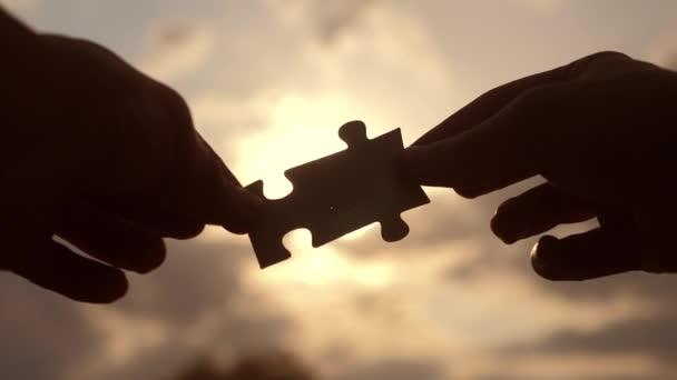 koncepce podnikových financí. mužské ruce spojují dvě hádanky s siluetou proti západu slunce. symbol spolupráce mezi přidružením a připojením. strategie životní styl podnikání