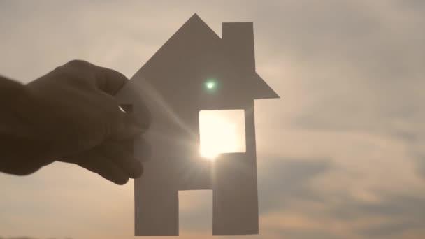 šťastný koncept výstavby rodinných domů. Muž, který drží doma v ruce dům s papírovým životním stylem za slunečních paprsků slunce. ekologie životní video symbol