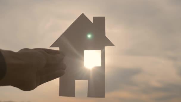 glücklich Familie Hausbau Konzept Lebensstil. Mann mit einem Papierhäuschen in der Hand im Sonnenuntergang. Ökologie Leben Video Symbol
