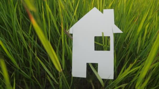 Bauen glückliche Familie Bau Haus Konzept. Papierhaus steht im grünen Gras in der Natur Lebensstil. Symbol Leben Ökologie Video