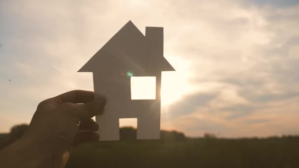boldog családi építőház koncepció életmód. ember, aki otthon a papír házat a kezében naplemente sziluett napfény. élet szimbóluma ökológia videó
