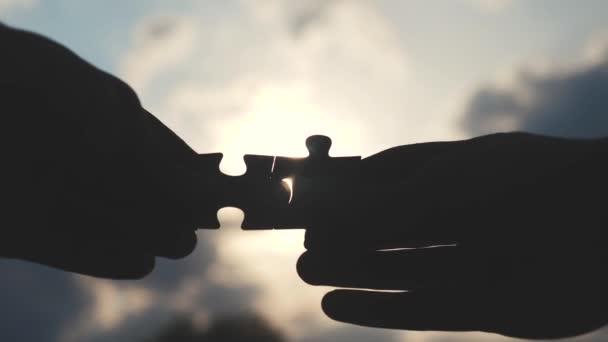 obchodní spolupráce koncepce podnikání koncept životní styl. mužské ruce spojují dvě hádanky s siluetou proti západu slunce. symbol týmové práce přidružení a připojení. strategie podnikání
