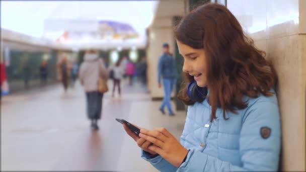 dospívající dívka s smartphone a sluchátky čekající na metro spousta lidí se v podzemí překřížit. koncept lidí v podzemních životním stylu metra. mladá dívka Bruneta dcera prohledá Internet na