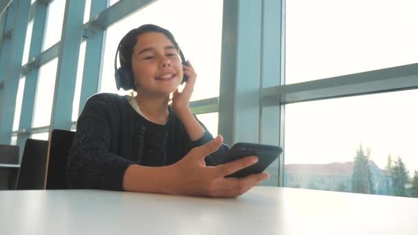 fiatal boldog tizenéves lány fejhallgató énekel, és hallgatta a zenét okostelefon. tinédzser lány a szociális hálózatok életmód hallgat zenét ül egy kávézóban