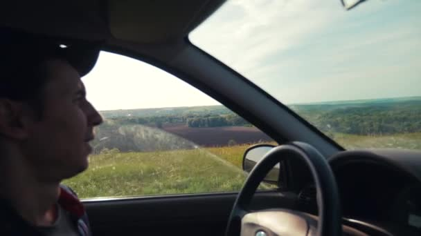 man driving a car on nature view from the window hills summer greens lifestyle . car journey trip concept