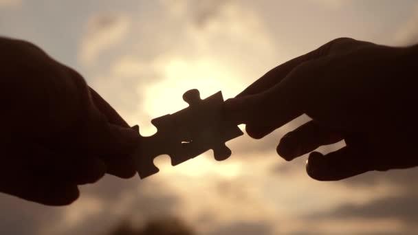 koncepce podnikových financí. mužské ruce spojují dvě hádanky s siluetou proti západu slunce. symbol spolupráce v souvislosti s asociací a životním stylem. strategie podnikání