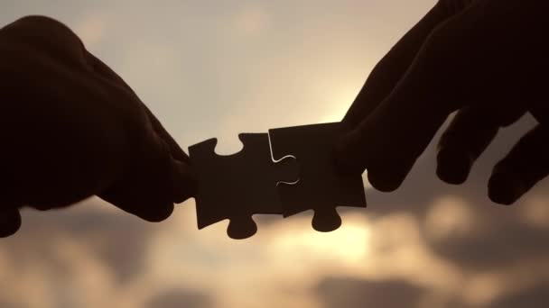 teamwork business finance concept lifestyle. male hands connect two puzzles silhouette against the sunset. symbol teamwork of association and connection. strategy business