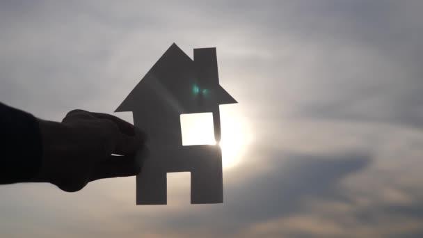 šťastný koncept rodinného stavebního domu. Muž, který v ruce drží v rukou dům s papírky životního stylu, který má při slunci siluetu slunce. životní ekologie symbol videa