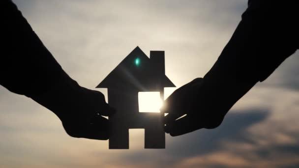 šťastný koncept rodinného stavebního domu. Muž, který drží doma papírový domek ve svém životním stylu za slunečních paprsků slunce. životní symbol ekologie video