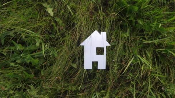 happy family construction house concept. lifestyle paper house stands in the green grass in nature. life symbol ecology video