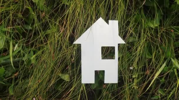 életmód boldog családi építőipari ház koncepcióját. papírház áll a zöld fű a természetben. szimbólum élet ökológia videó