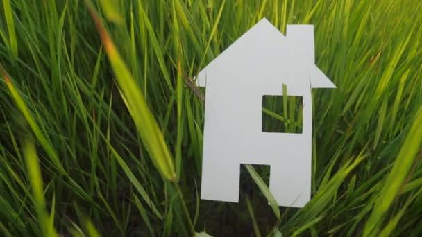 Bauen glückliche Familie Bau Haus Konzept. Papierhaus steht im grünen Lifestyle-Gras in der Natur. Symbol Leben Ökologie Video