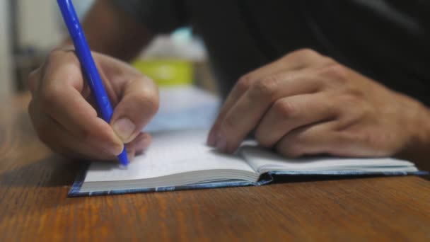 man writes in notebook. male hand writing in a notepad lifestyle . concept business education. man makes notes in notebook that lies on the table
