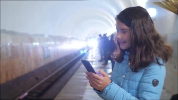 dívčí teenager v podzemní dráze metra v metru, čekající na příjezd vlaku, má telefon Smartphone. malá holčička bruneta, hledá Internet na webových stránkách životního stylu sociální sítě