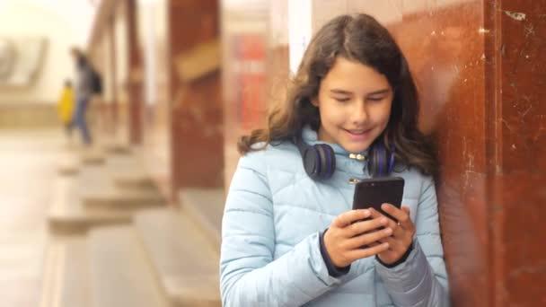 dívčí puberťatka v podzemním metra v metru, která čeká na příjezd vlaku, má telefon Smartphone. malá holčička bruneta dcera prohledá Internet na webových sociálních sítích.