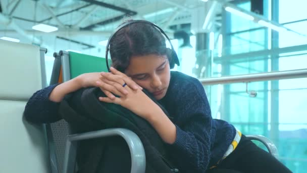 Tired girl teen in headphones traveler sleeping on the airport waiting for the plane departure gates bench with all her luggage by her side. young girl daughter waiting lifestyle hall room Tiring