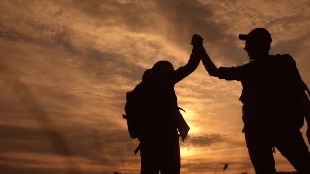 teamwork business journey concept win. happy family team tourists man and woman sunset silhouette help shake hands victory success . slow motion video. tourism husband and lifestyle wife on top of the