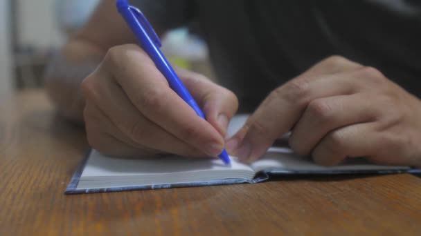 man writes in notebook. male hand writing in a notepad. concept business education. man makes notes in notebook that lies on the table lifestyle