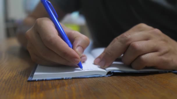 man writes in notebook. male hand writing in a notepad. concept business education. man makes notes in notebook that lies on lifestyle the table