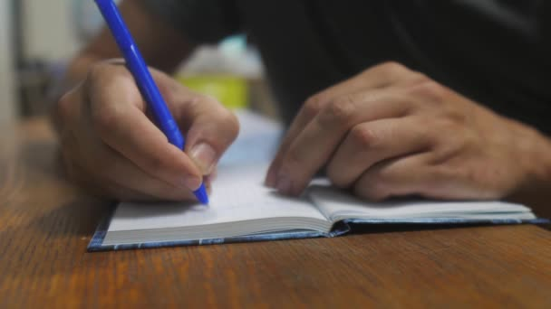 man writes in notebook. male hand writing in a notepad. concept business lifestyle education. man makes notes in notebook that lies on the table