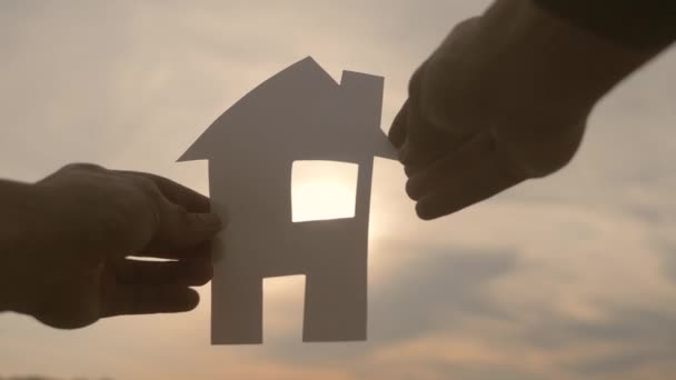šťastný koncept výstavby rodinných domů. Muž, který drží doma papírový domek ve svých rukou při slunečním svitu siluetě. Ekologie život video životní styl symbol