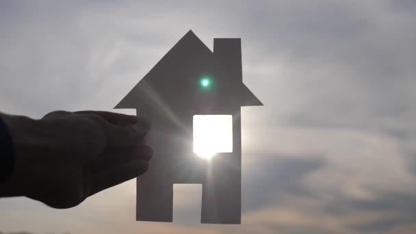 šťastný koncept výstavby rodinných domů. mužským životním stylem, který drží doma papírový domek ve svých rukou při slunci s siluetou slunce. ekologie životní video symbol