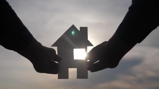 šťastný koncept rodinného stavebního domu. Muž, který drží doma papírový domek ve svých rukou při životním stylu slunce, silueta slunečního svitu. životní symbol ekologie video