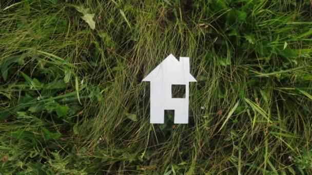 boldog családi építőház koncepció életmód. papírház áll a zöld fű a természetben. élet szimbóluma ökológia videó
