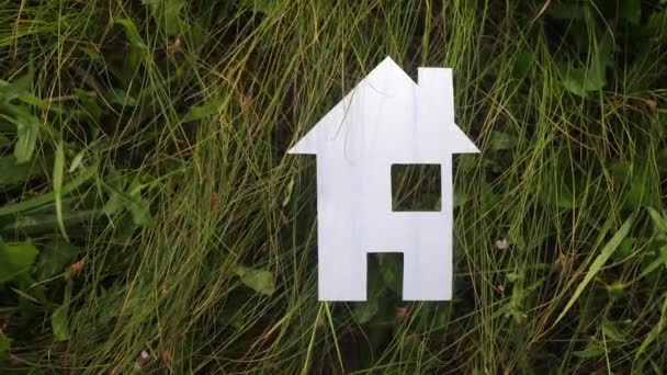 boldog család építőipari ház életmód koncepció. papírház áll a zöld fű a természetben. szimbólum élet ökológia videó