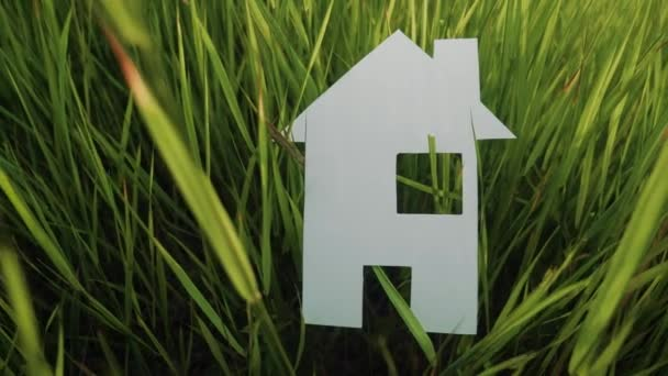 building happy family construction house concept. paper house stands in the green grass in nature. lifestyle symbol life ecology video