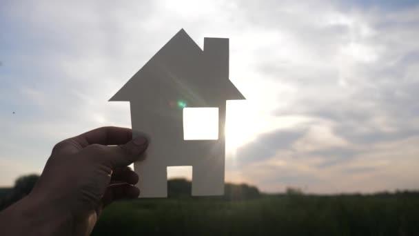 šťastný koncept rodinného stavebního domu. mužským životním stylem, který drží doma papírový domek ve svých rukou při slunci s siluetou slunce. životní symbol ekologie video