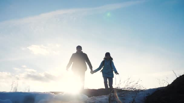 happy family dad with daughter teamwork tourists silhouette concept. slow motion video. dad and daughter with backpacks run up the hill and jump. man and young lifestyle girl walking hiking