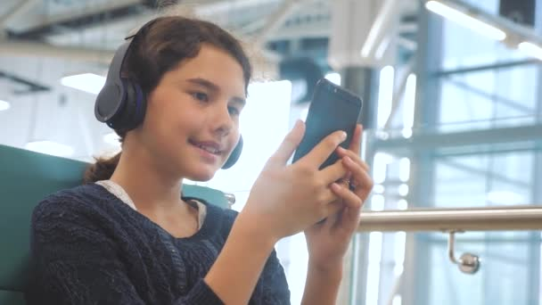 airport waiting hall room for a flight by plane. young happy teen girl in headphones listening to lifestyle the music on smartphone chatting communicates in the messenger. teenager girl in social