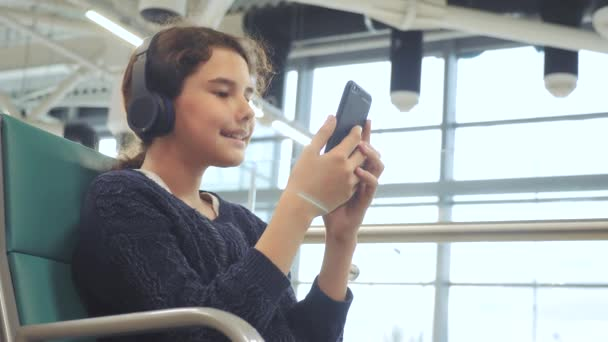 airport waiting hall room for a flight by plane. lifestyle young happy teen girl in headphones listening to the music on smartphone chatting communicates in the messenger. teenager girl in social