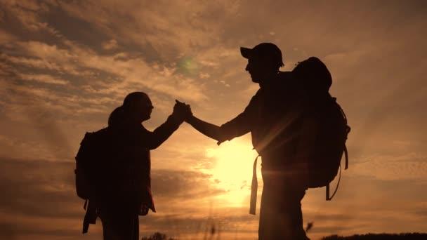 Teamwork-Business-Travel-Konzept gewinnen. Team Touristen Mann und Frau Lifestyle Sonnenuntergang Silhouette helfen, Hände zu schütteln Erfolg Sieg. Zeitlupenvideo. Tourismus Mann und Frau auf dem Gipfel des Berges