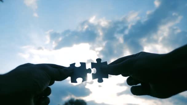 koncepce podnikových financí. mužské ručičky spojují dvě hádanky s siluetou životního stylu západu slunce. symbol týmové práce přidružení a připojení. obchodní strategie