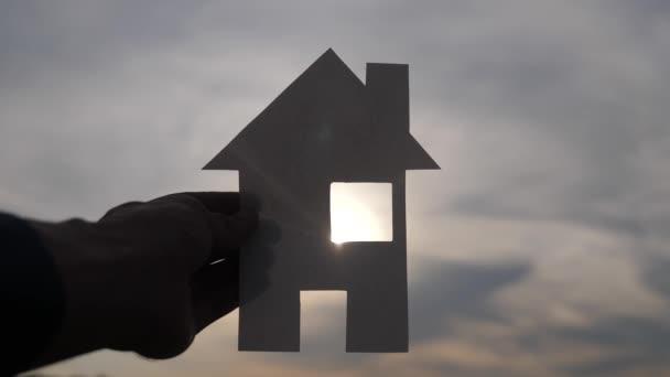 šťastný životní styl rodinný dům koncept. Muž, který drží doma papírový domek ve svých rukou při slunečním svitu siluetě. životní ekologie symbol videa