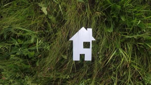 glückliche Familie Bau Haus Konzept. Papierhaus steht im grünen Gras Lebensstil in der Natur. Leben Symbol Ökologie Video