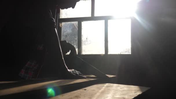 Tesař ručně dělený životní styl a řemeslné pojetí pomalé video. Tesař řezající strom v dílně, která se při řezání slunečního světla Rýsová na okenní siluetě. dřevořezník zapojený do zpracování dřeva na