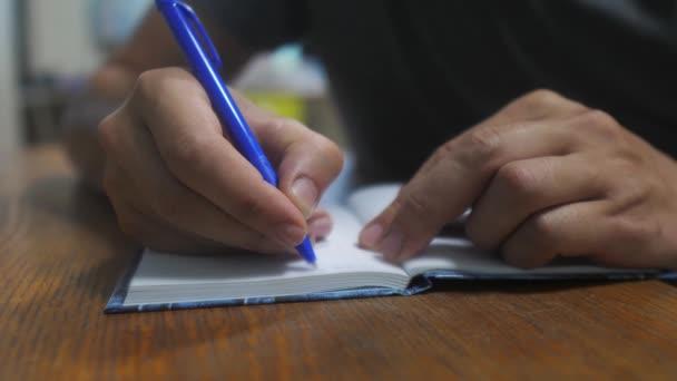 ember leír-ban jegyzetfüzet. férfi kézzel írt egy jegyzettömböt. koncepció üzleti oktatás. ember ideiglenes tákolmány jegyzék-ban jegyzetfüzet amit fekszik életmód az asztalon