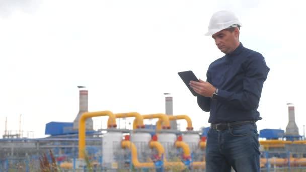 Teamwork Gasproduktionsstationskonzept. Engineering Mann steht mit digitalen Tablet weißen Schutzhelm. Mann Ingenieur in Helmarbeit am Bahnhof studieren auf einem Gas-Lifestyle-Versorgungsgeschäft