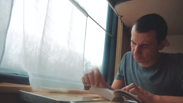 man reading a book in a train long journey. railroad travel concept coach train journey. view beautiful from the window of lifestyle a moving train railway Russia winter. interior inside train