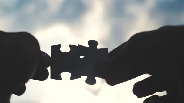 koncepce podnikových financí. mužské ruce spojují dvě hádanky s siluetou proti západu slunce. symbol týmové práce přidružení a připojení. strategie životní styl podnikání