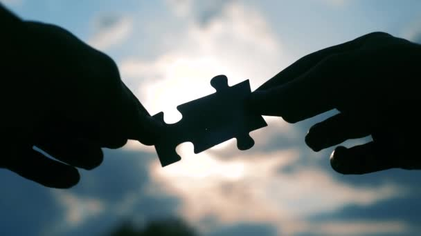 teamwork business finance concept. male hands connect two puzzles silhouette against the sunset. symbol teamwork of association and connection. strategy business lifestyle