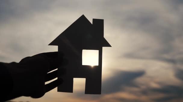 šťastný rodinný domek styl stavby. Muž, který drží doma papírový domek ve svých rukou při slunečním svitu siluetě. životní ekologie symbol videa