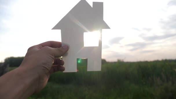 boldog családi építőház koncepció. ember, aki otthon egy életmód papírházat a kezében naplemente sziluett napfény. élet szimbóluma ökológia videó