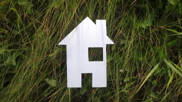 happy family construction house concept. paper house stands in the green grass in nature. life lifestyle symbol ecology video