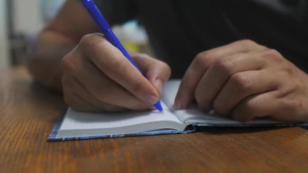man writes in notebook. male hand writing in a notepad. concept business education. man makes notes in lifestyle notebook that lies on the table