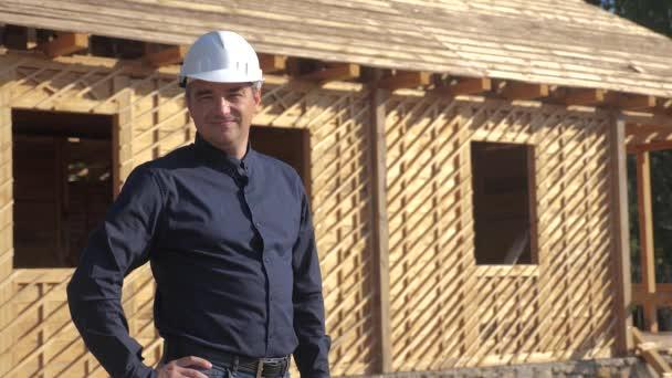 Konzept Gebäude Architekt Zeitlupe Video. Bauarbeiter mit Helm steht an einer Konstruktion, auf der ein Plan steht. Grundstück in der Nähe eines im Bau befindlichen Fachwerkhauses. Arbeiter arbeitet bei einem