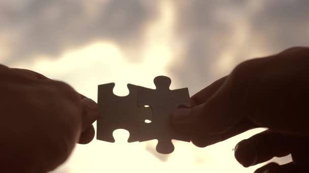 koncepce podnikových financí. mužské ruce spojují dvě hádanky s siluetou proti západu slunce. symbol týmové práce přidružení a připojení. strategický životní styl